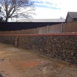 Flint wall rebuild and repair, with red brick coping stones, Priory Gardens in Royston
